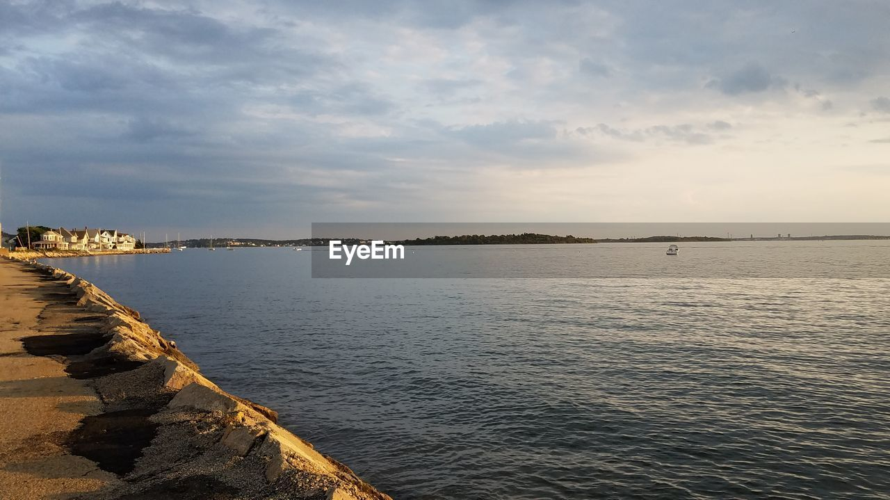 water, sky, cloud - sky, scenics - nature, tranquil scene, beauty in nature, tranquility, sea, nature, no people, architecture, outdoors, non-urban scene, idyllic, waterfront, day, sunset, built structure, rock, groyne
