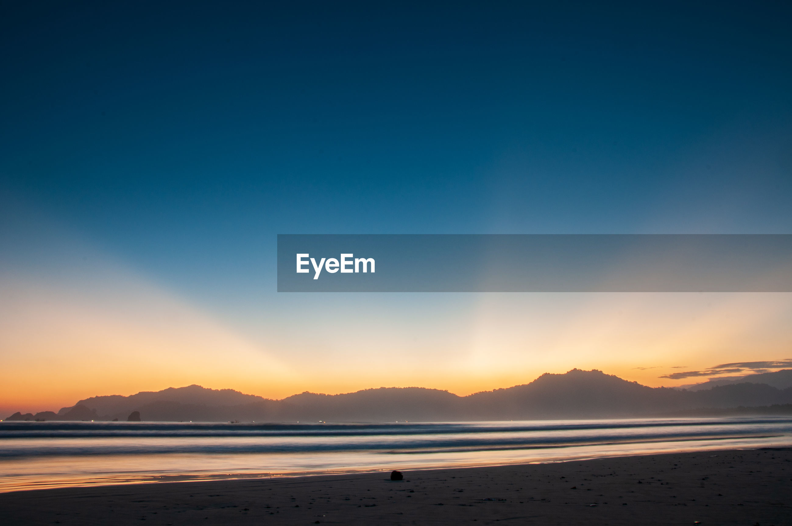 SCENIC VIEW OF SEA AGAINST BLUE SKY DURING SUNSET