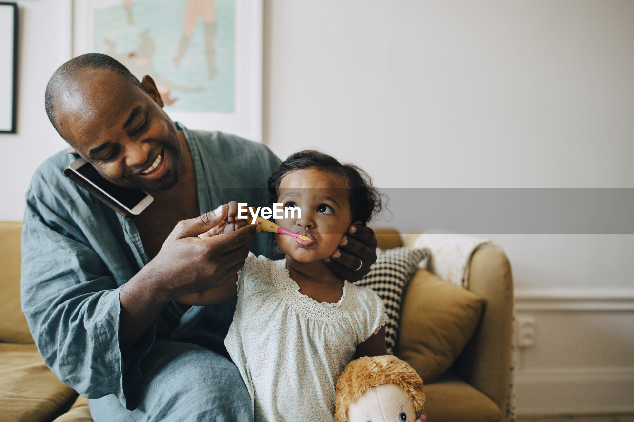 PORTRAIT OF FATHER AND SON SITTING ON SOFA