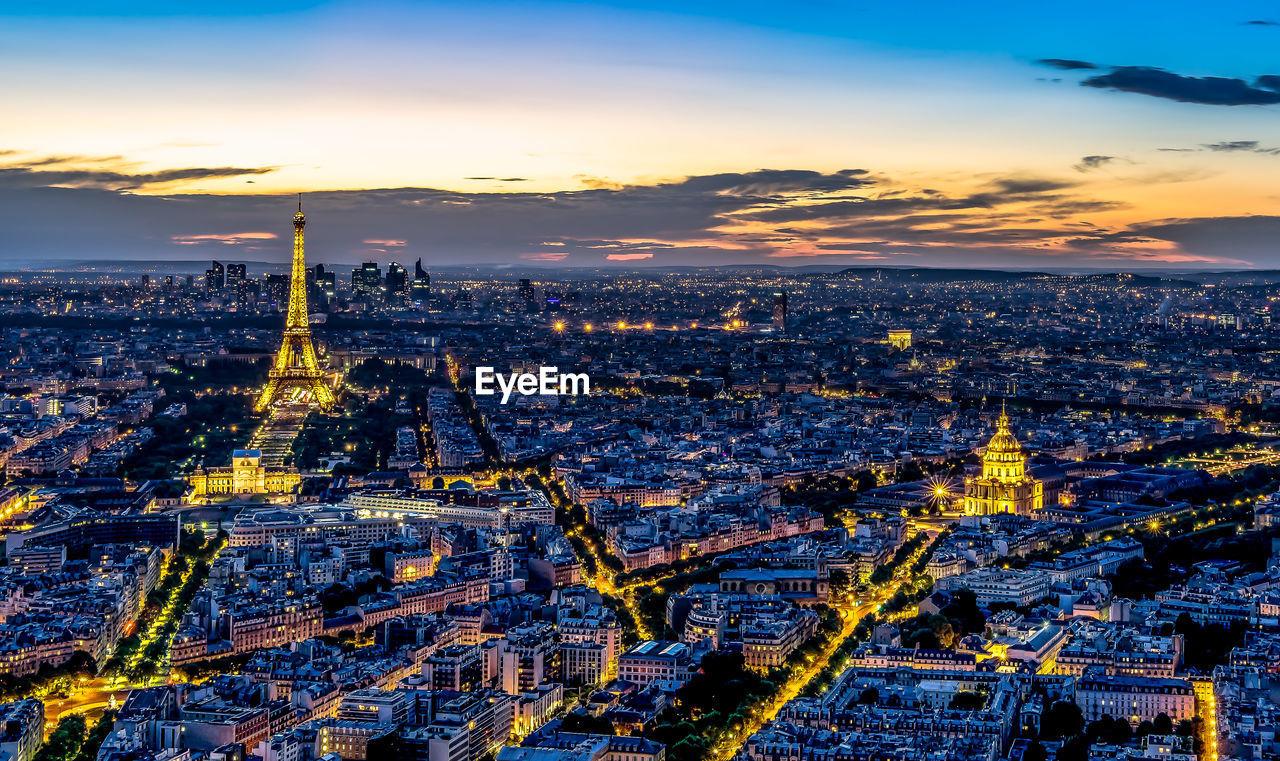 Eiffel tower amidst cityscape at dusk