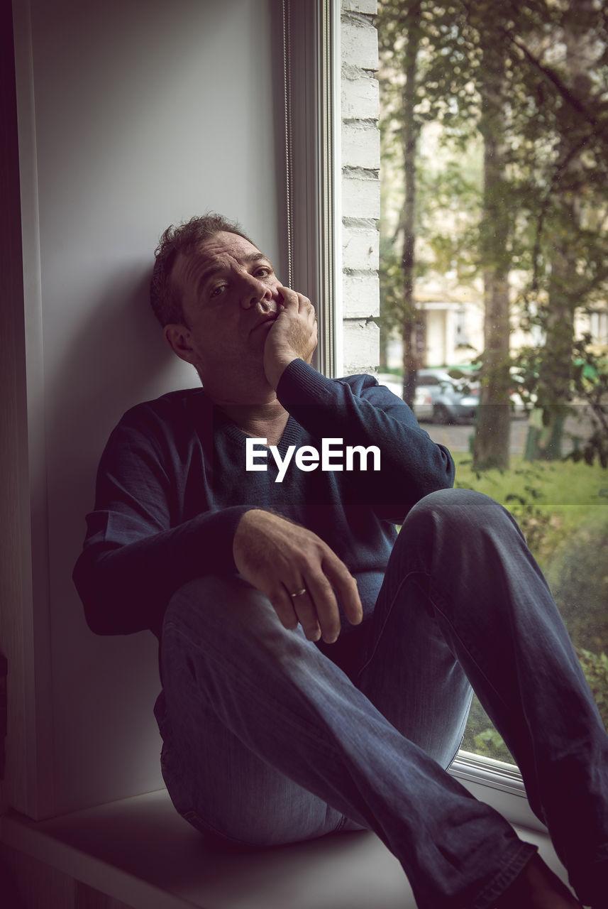 Portrait Of Sad Mature Man With Hand On Chin Sitting At Window Sill