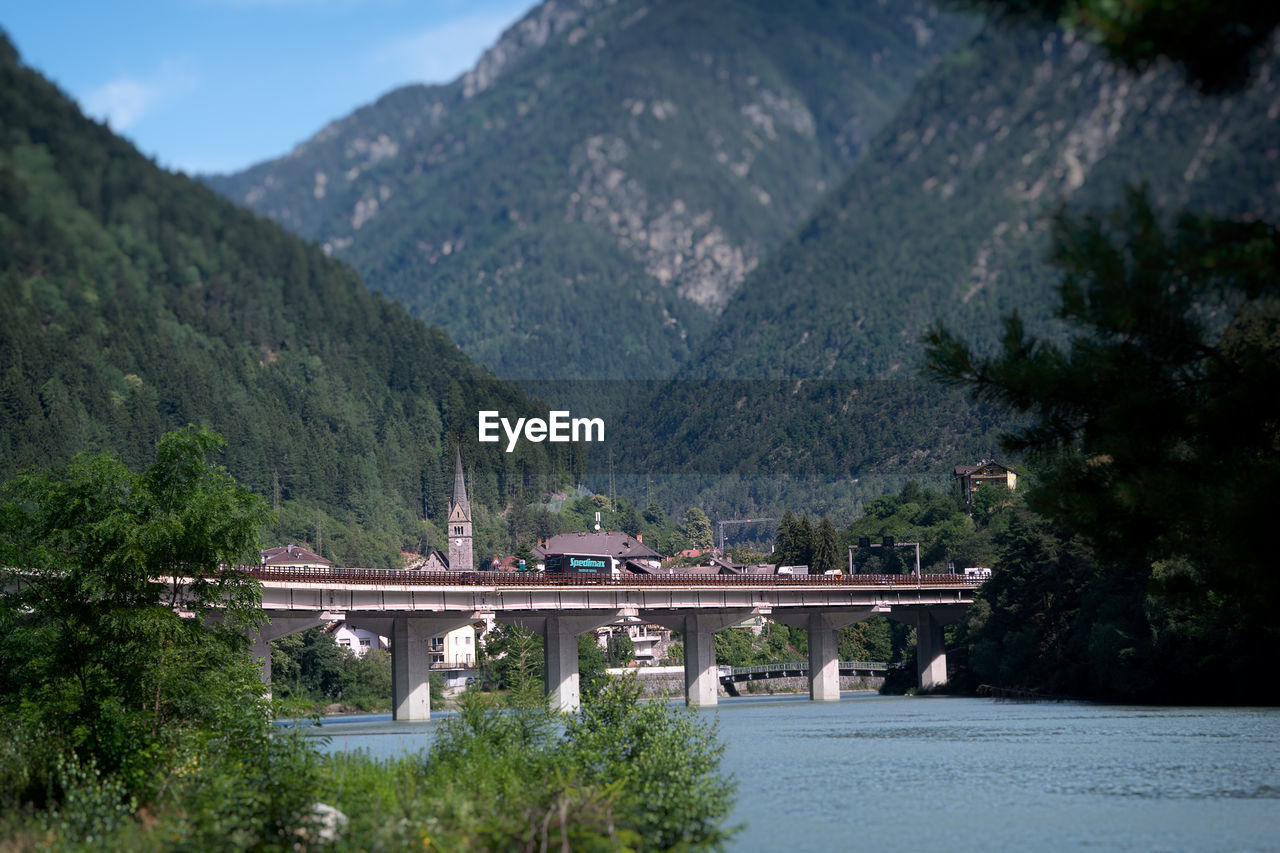 tree, mountain, plant, water, scenics - nature, nature, built structure, transportation, beauty in nature, architecture, mountain range, no people, day, connection, river, growth, bridge, tranquil scene, bridge - man made structure, outdoors