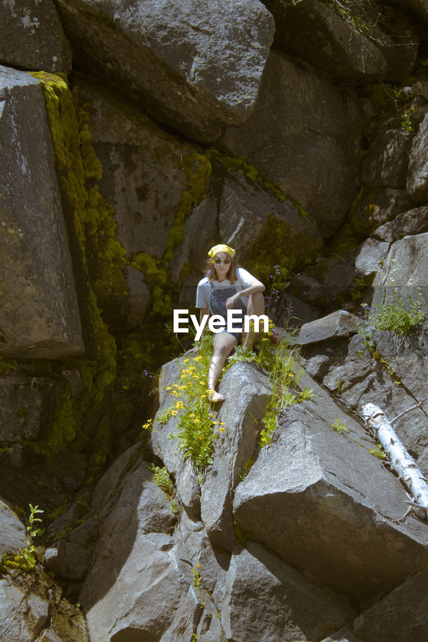 LOW ANGLE VIEW OF WOMAN STANDING ON ROCK AGAINST ROCKS