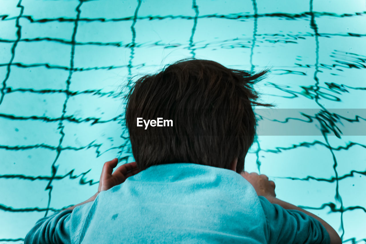 Rear view of boy dipping head in swimming pool
