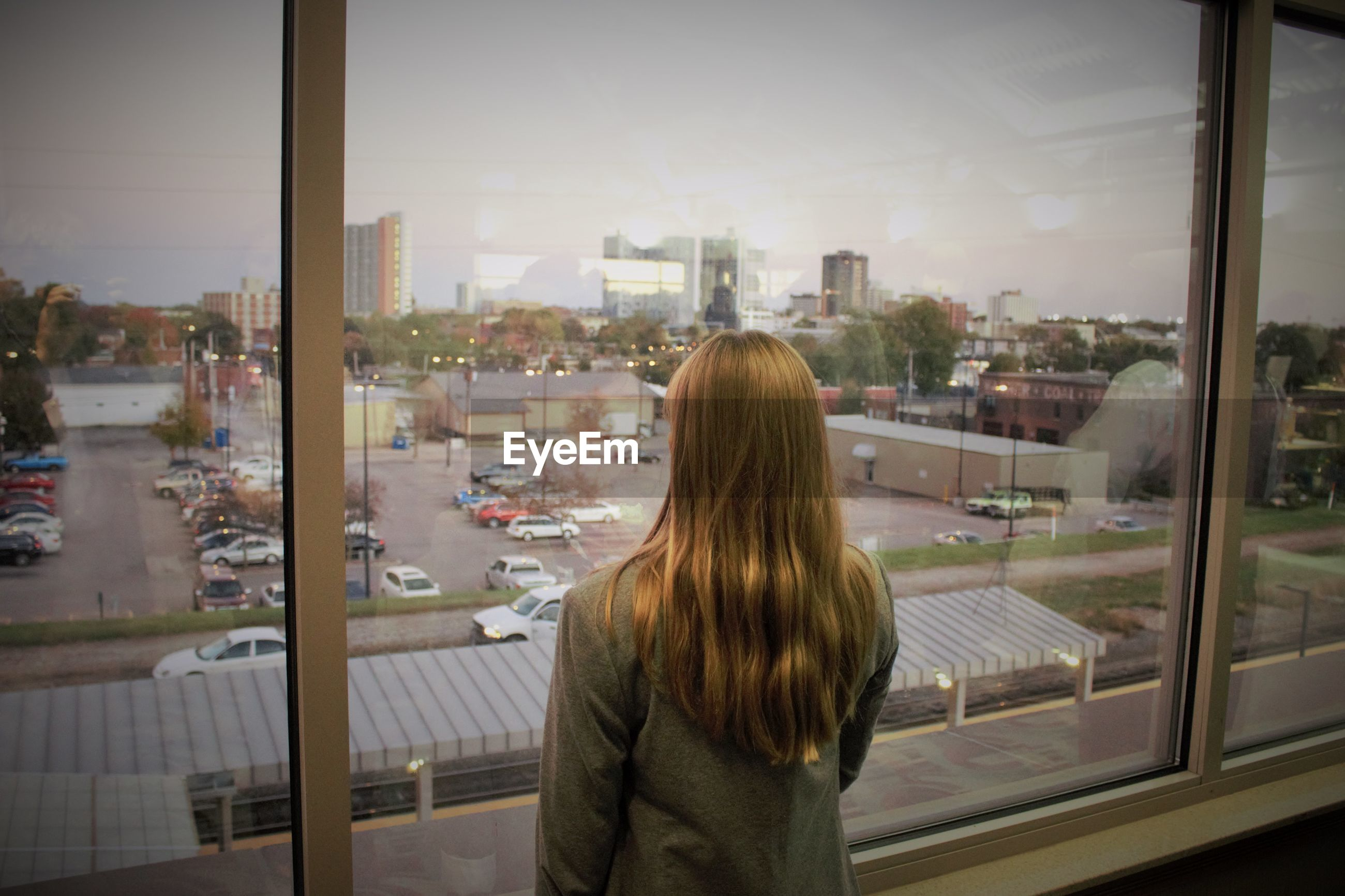 Rear view of blond woman looking through building window