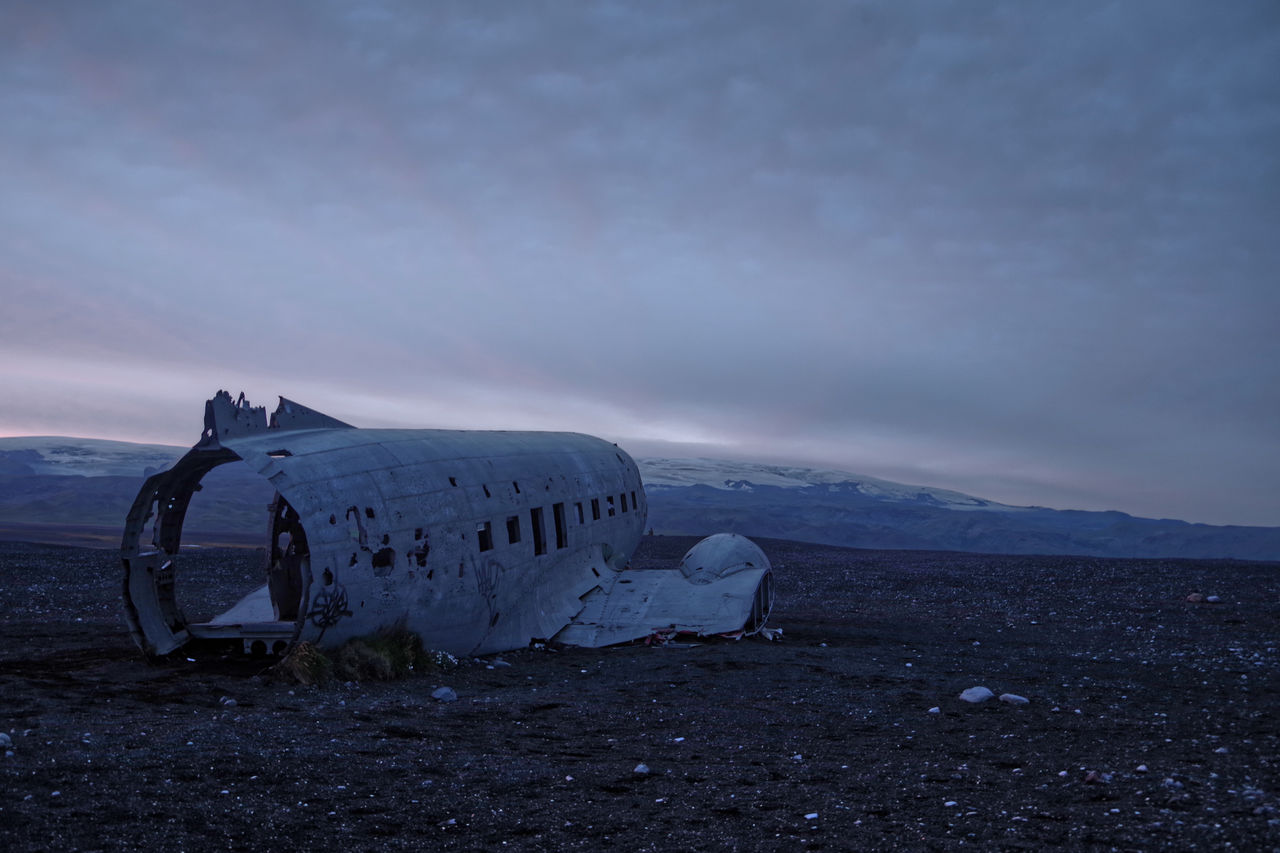 Damaged airplane on land against sky