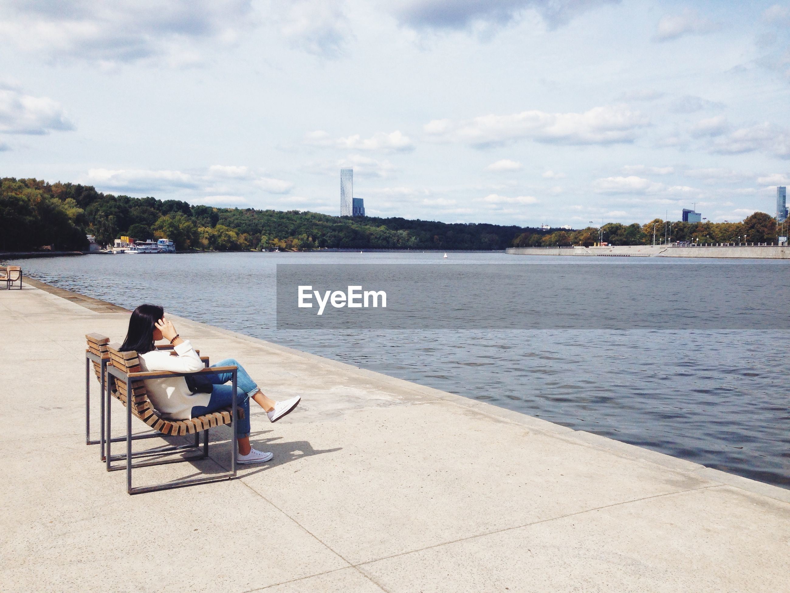 Woman sitting on bench against river in city