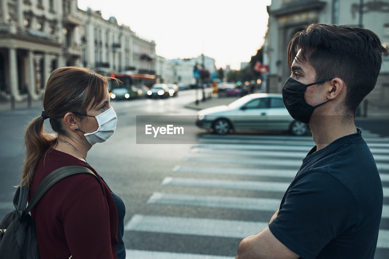 Man and woman talking and waiting at pedestrian crossing in the city center wearing the face masks