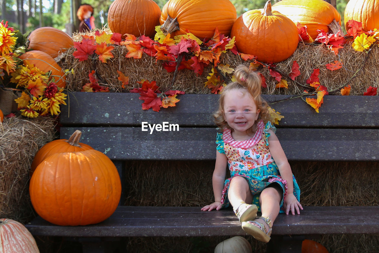 Portrait Of Girl Smiling On Bench By Pumpkins At Park During Autumn