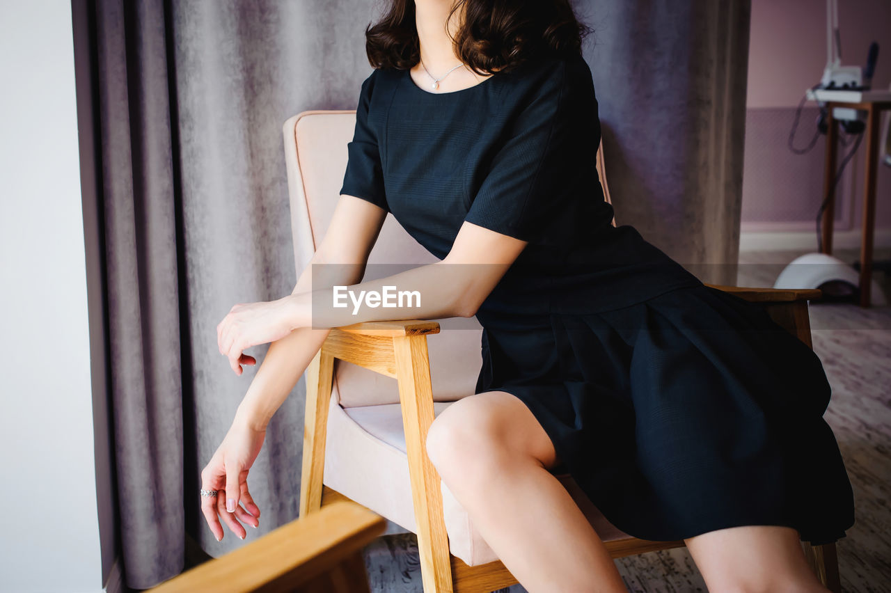 Midsection Of Young Woman In Black Dress Sitting On Armchair At Home