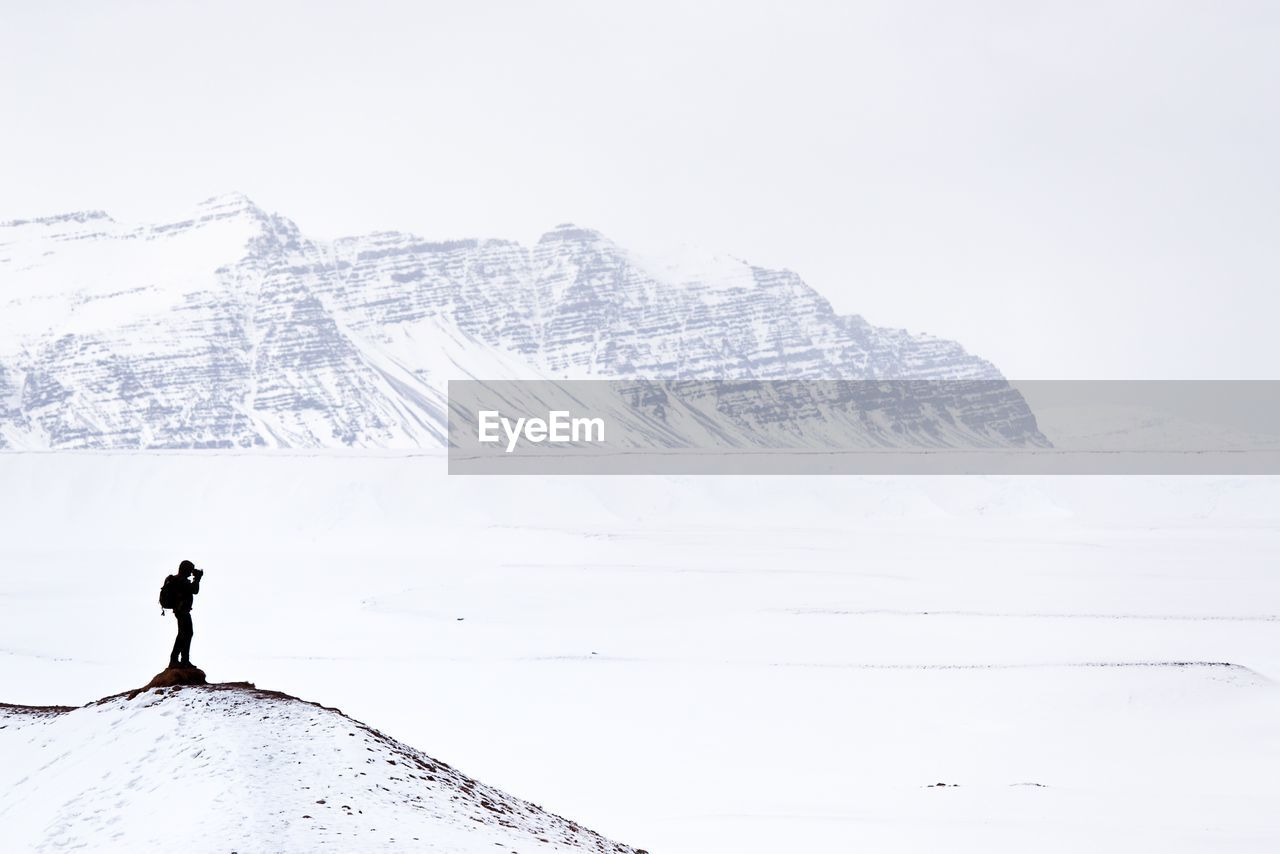 MAN STANDING ON SNOW COVERED MOUNTAIN AGAINST CLEAR SKY