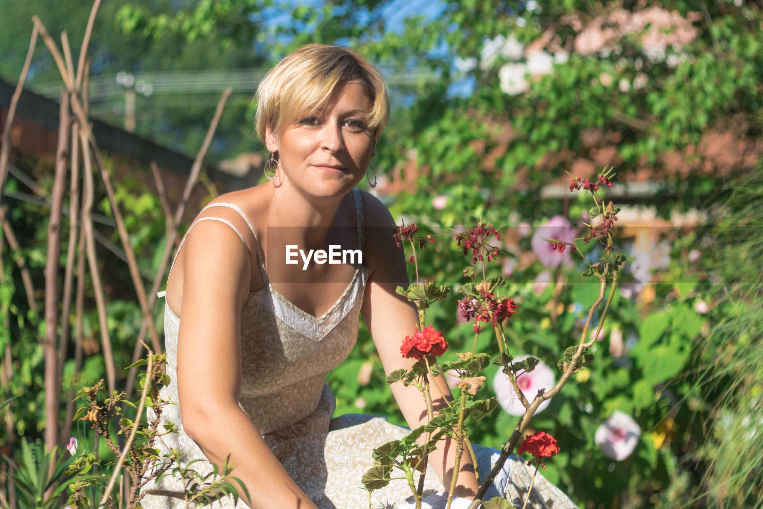 Portrait of smiling woman gardening in back yard