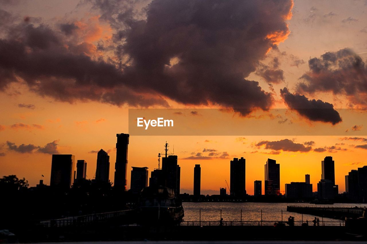 sunset, architecture, building exterior, skyscraper, built structure, sky, city, orange color, cityscape, travel destinations, urban skyline, cloud - sky, skyline, silhouette, modern, development, waterfront, dramatic sky, no people, water, outdoors, sea, nature, growth, tall, scenics, beauty in nature