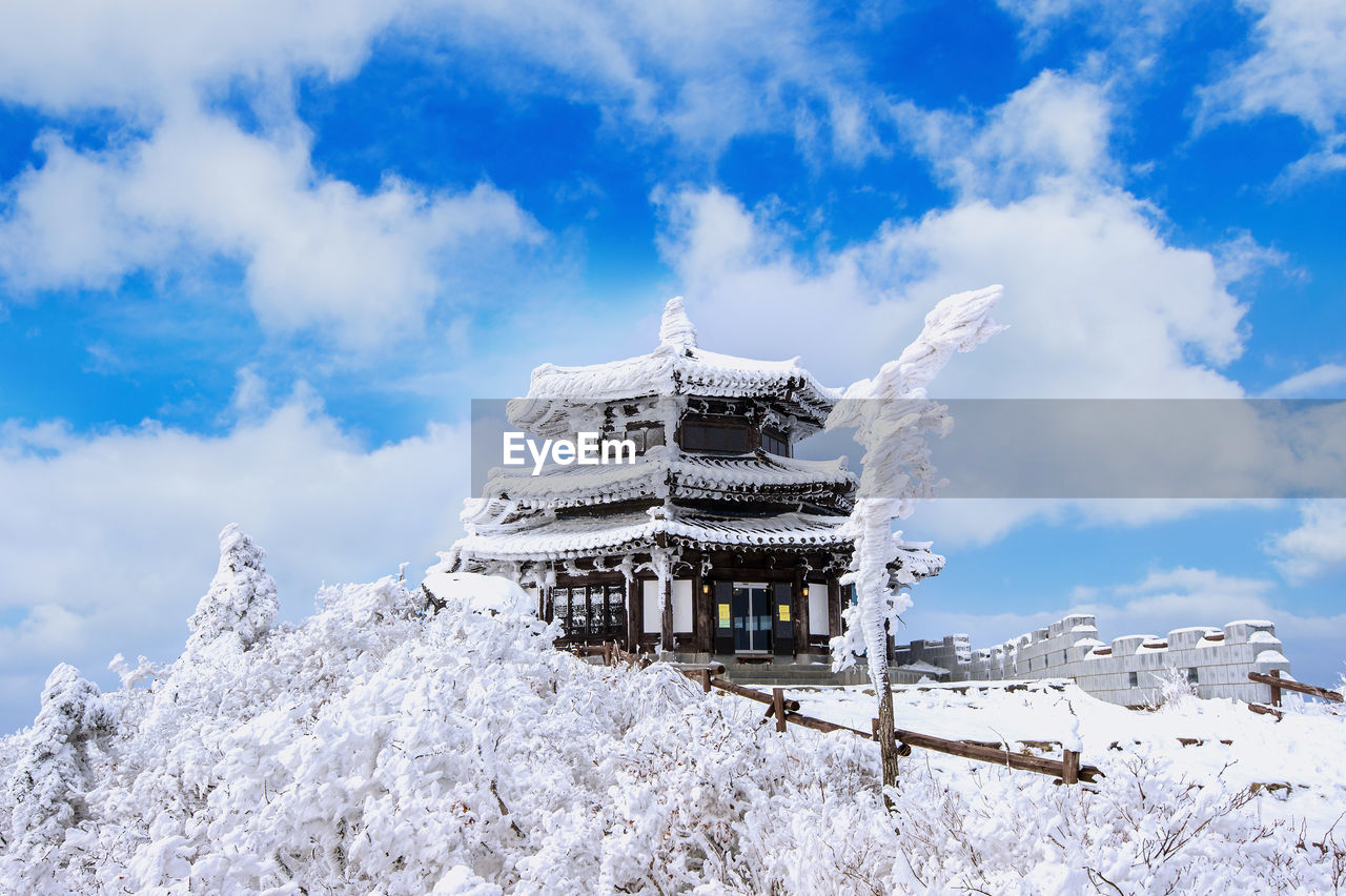 snow, cloud - sky, winter, cold temperature, sky, built structure, architecture, nature, white color, religion, building exterior, place of worship, belief, spirituality, day, beauty in nature, building, no people, low angle view, outdoors, snowcapped mountain