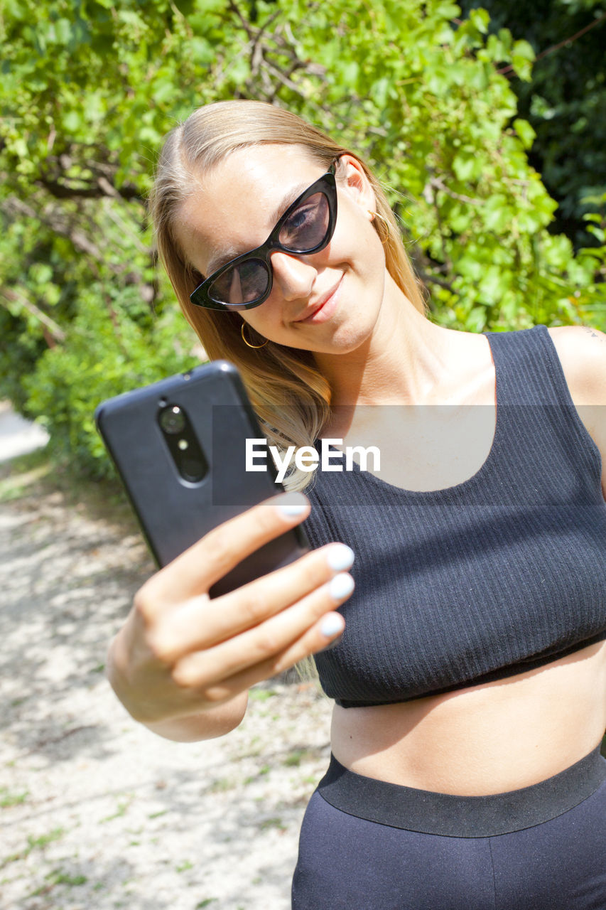 sunglasses, glasses, mobile phone, wireless technology, one person, fashion, smart phone, holding, real people, technology, adult, using phone, front view, young adult, lifestyles, women, young women, portable information device, telephone, outdoors, hairstyle