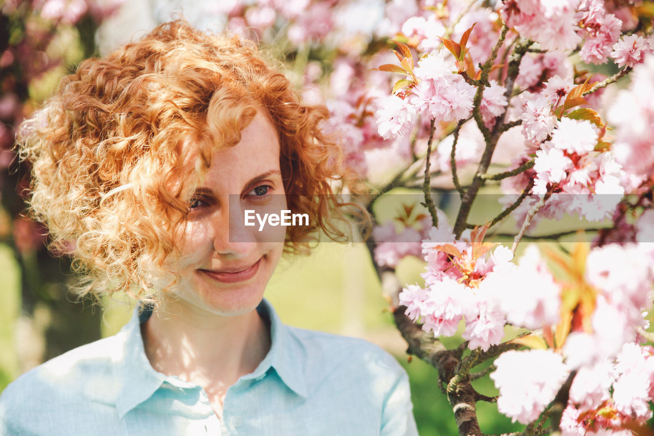 Close-up of smiling woman by blossoms on branch in park