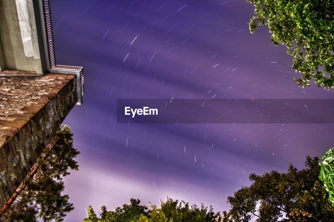 Low angle view of star trails in sky at night