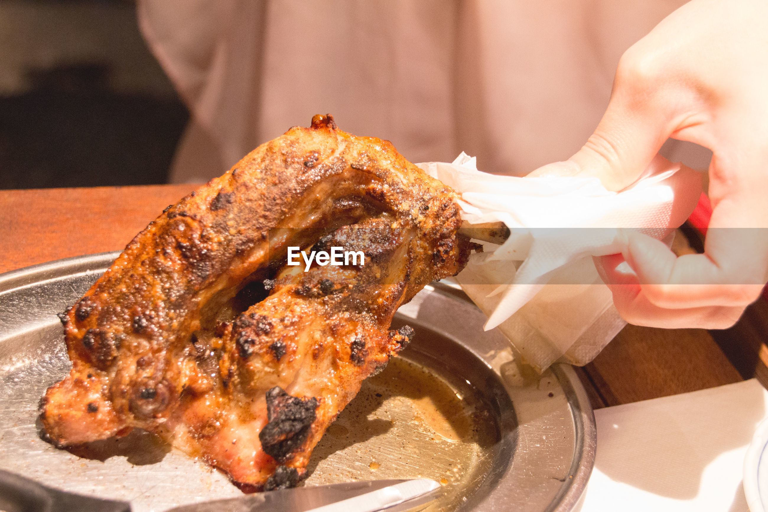 Close-up of womans hand holding roast chicken