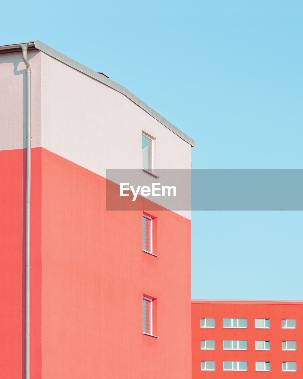 architecture, built structure, building exterior, copy space, building, clear sky, low angle view, sky, red, no people, window, blue, day, nature, wall - building feature, white color, city, outdoors, residential district, orange color, apartment