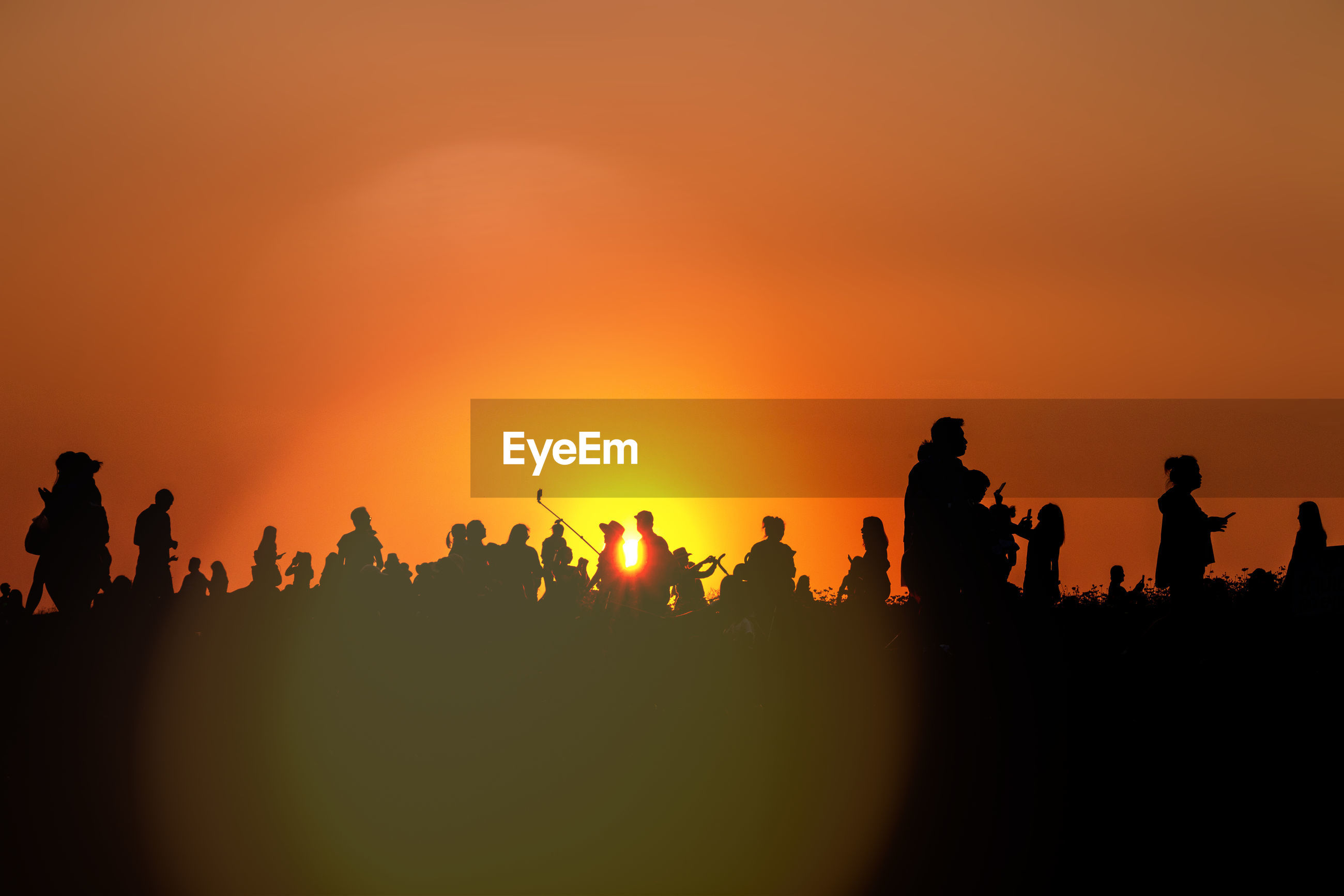 Silhouette people on field against clear orange sky
