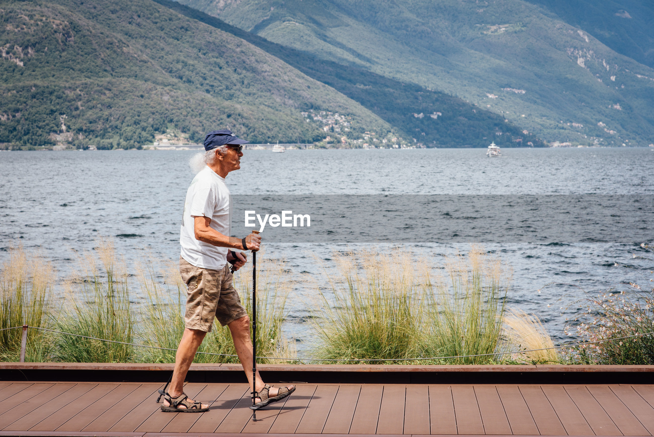 water, full length, standing, one person, lake, day, adult, leisure activity, mountain, casual clothing, nature, cap, men, holding, holiday, side view, looking, outdoors, shorts, looking at view, contemplation