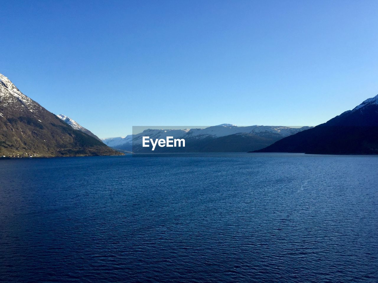 water, scenics - nature, beauty in nature, mountain, tranquil scene, sky, waterfront, tranquility, blue, copy space, clear sky, idyllic, mountain range, day, no people, nature, sea, non-urban scene, outdoors, mountain peak, range