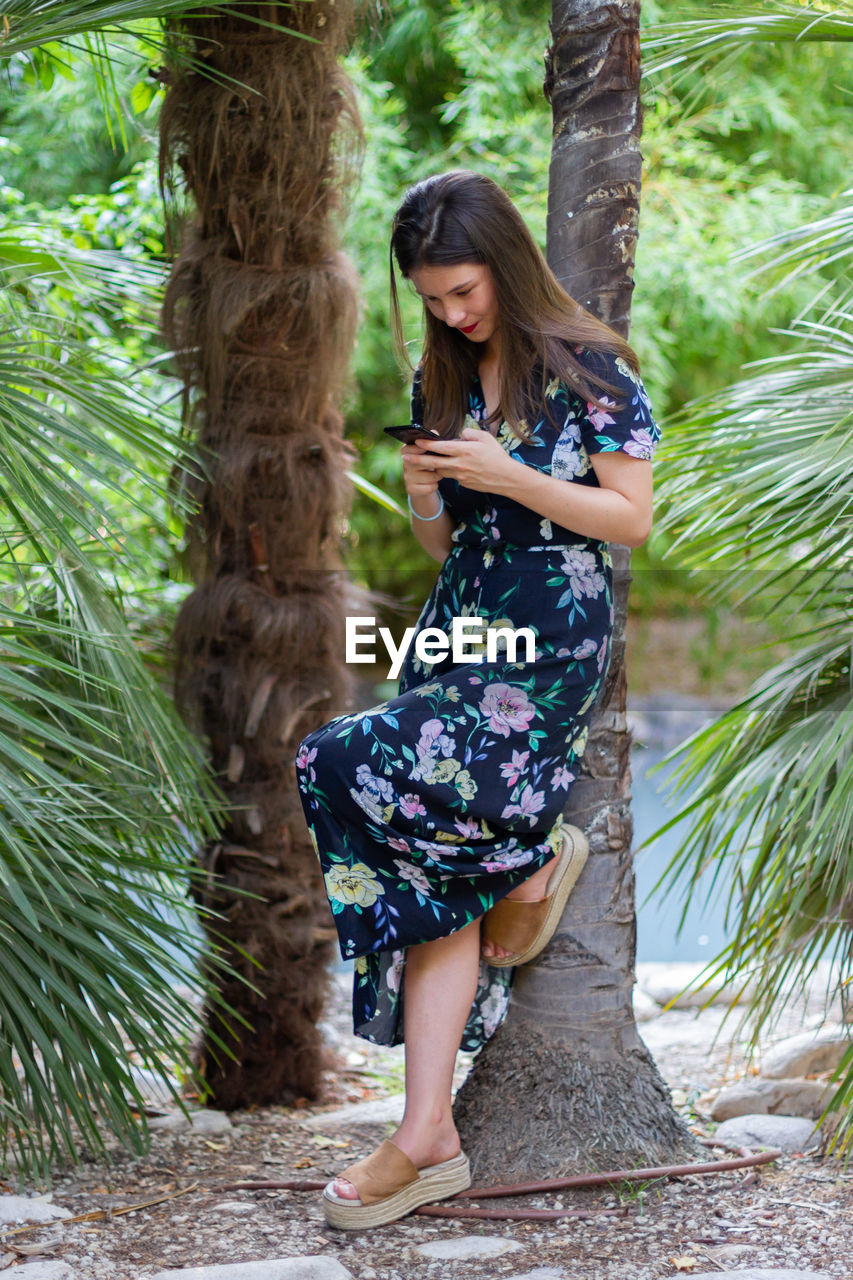 Full length of woman using mobile phone while standing by tree trunk