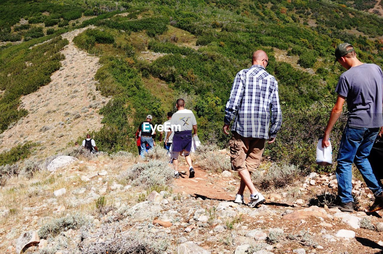 real people, hiking, adventure, men, walking, leisure activity, rear view, casual clothing, mountain, lifestyles, backpack, nature, medium group of people, women, vacations, standing, day, outdoors, group of people, full length, togetherness, beauty in nature, teamwork, people, adult, adults only