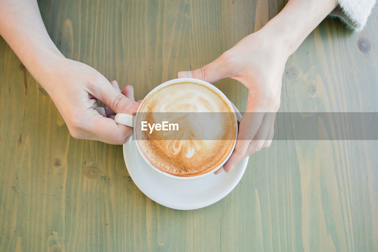 coffee, cup, food and drink, refreshment, mug, drink, coffee cup, human hand, coffee - drink, real people, hand, frothy drink, table, one person, human body part, holding, lifestyles, leisure activity, women, cappuccino, hot drink, crockery, latte, finger