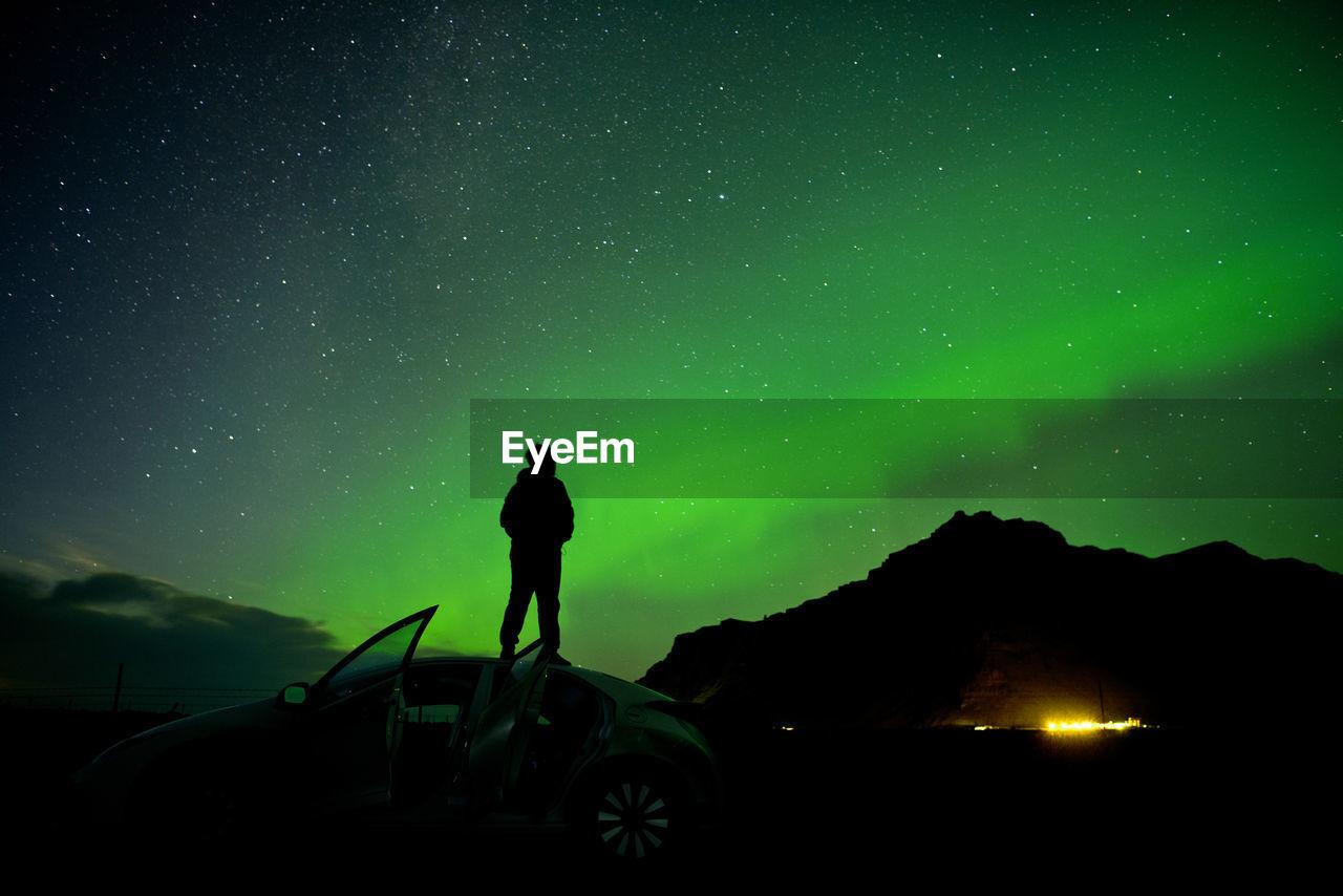 Silhouette Man Standing On Car Roof Against Aurora Borealis