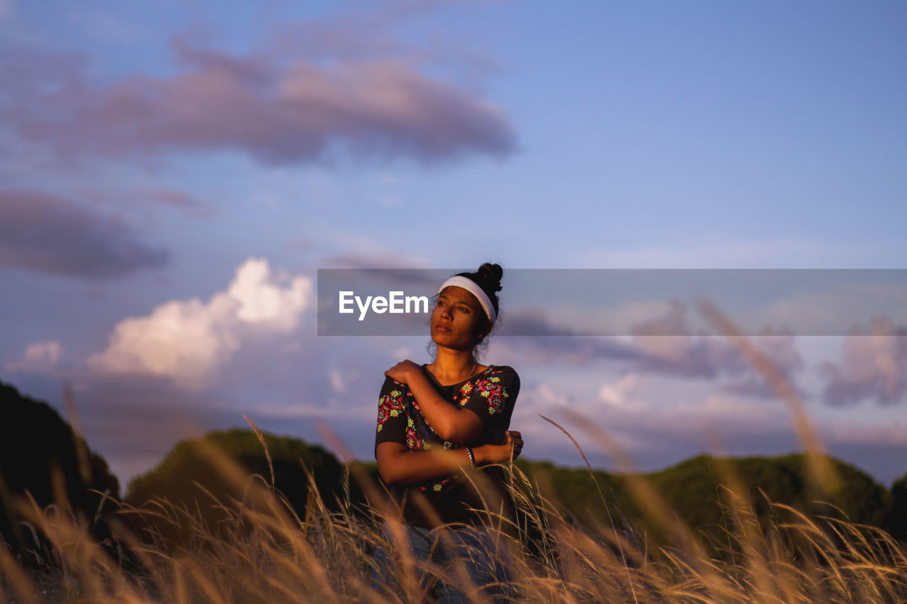 Woman sitting on field against sky during sunset