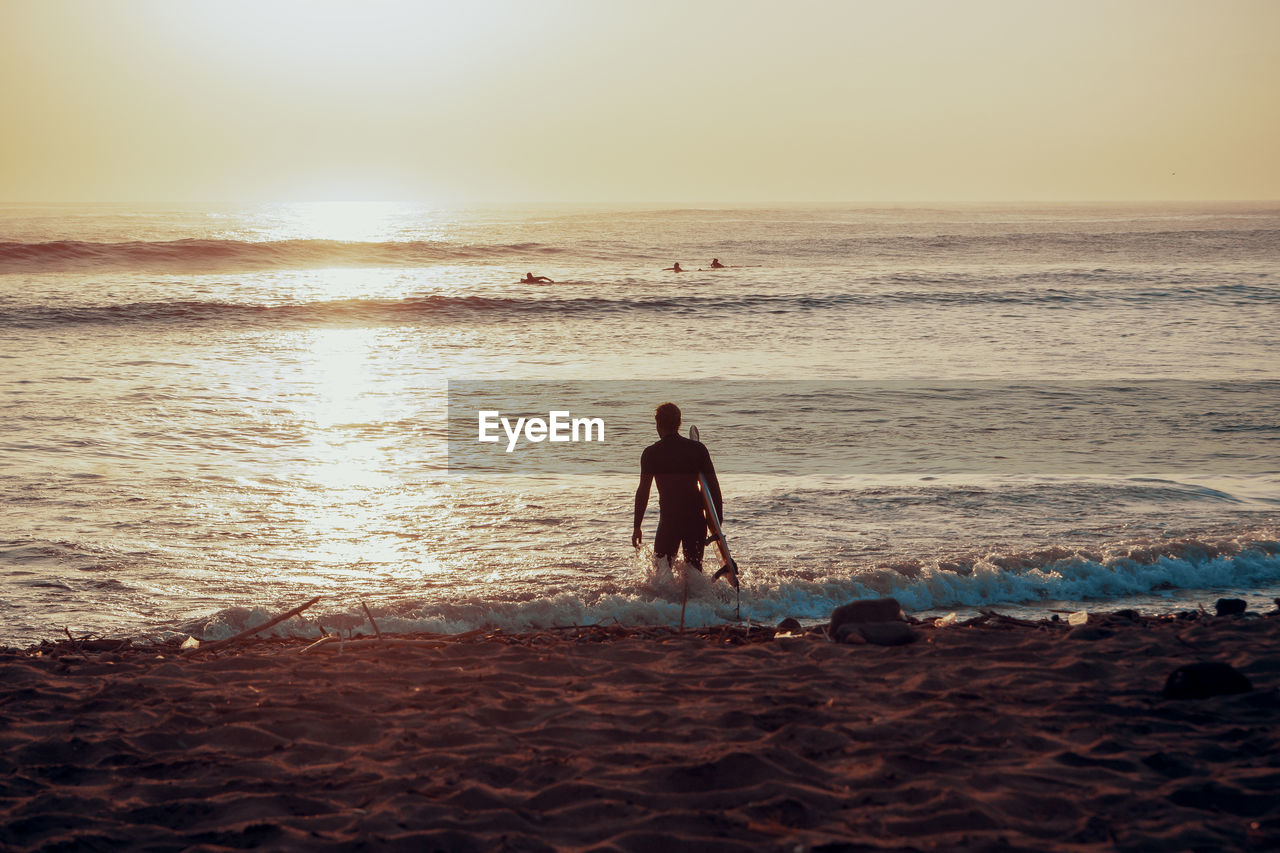 sea, beach, water, land, sky, horizon, horizon over water, real people, lifestyles, beauty in nature, leisure activity, scenics - nature, one person, rear view, nature, vacations, sunset, men, outdoors