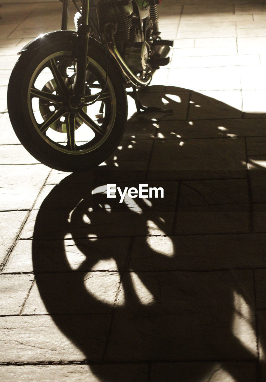 shadow, sunlight, footpath, bicycle, transportation, day, nature, wheel, mode of transportation, outdoors, land vehicle, street, sunny, city, flooring, real people, one person, high angle view, focus on shadow, paving stone, tiled floor