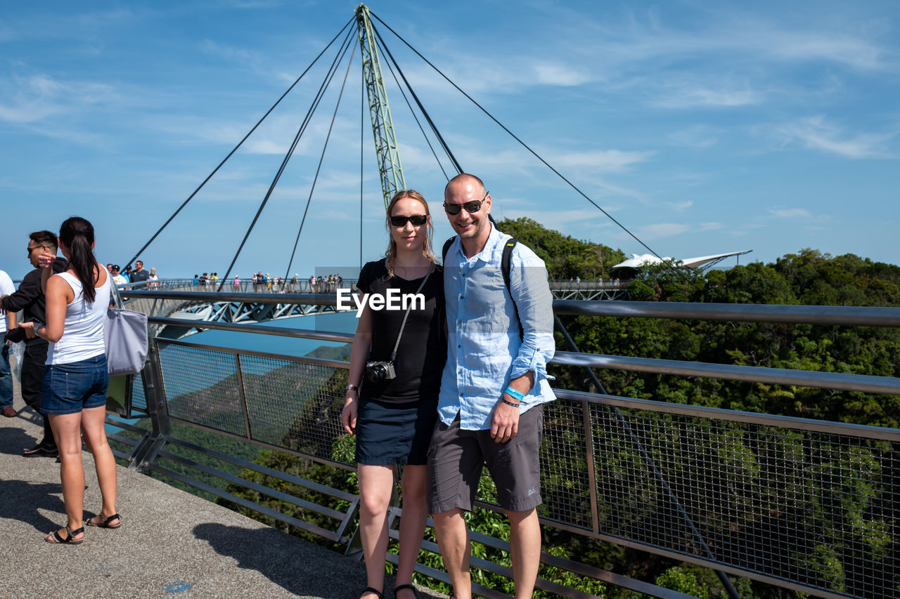 sky, real people, full length, lifestyles, standing, men, front view, leisure activity, nature, young men, casual clothing, young adult, connection, togetherness, cloud - sky, architecture, railing, looking at camera, day, bridge - man made structure, outdoors