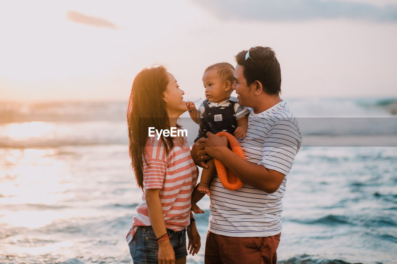 child, water, childhood, family, sea, beach, parent, togetherness, males, females, men, women, group of people, bonding, real people, love, leisure activity, standing, casual clothing, positive emotion, son, daughter, innocence