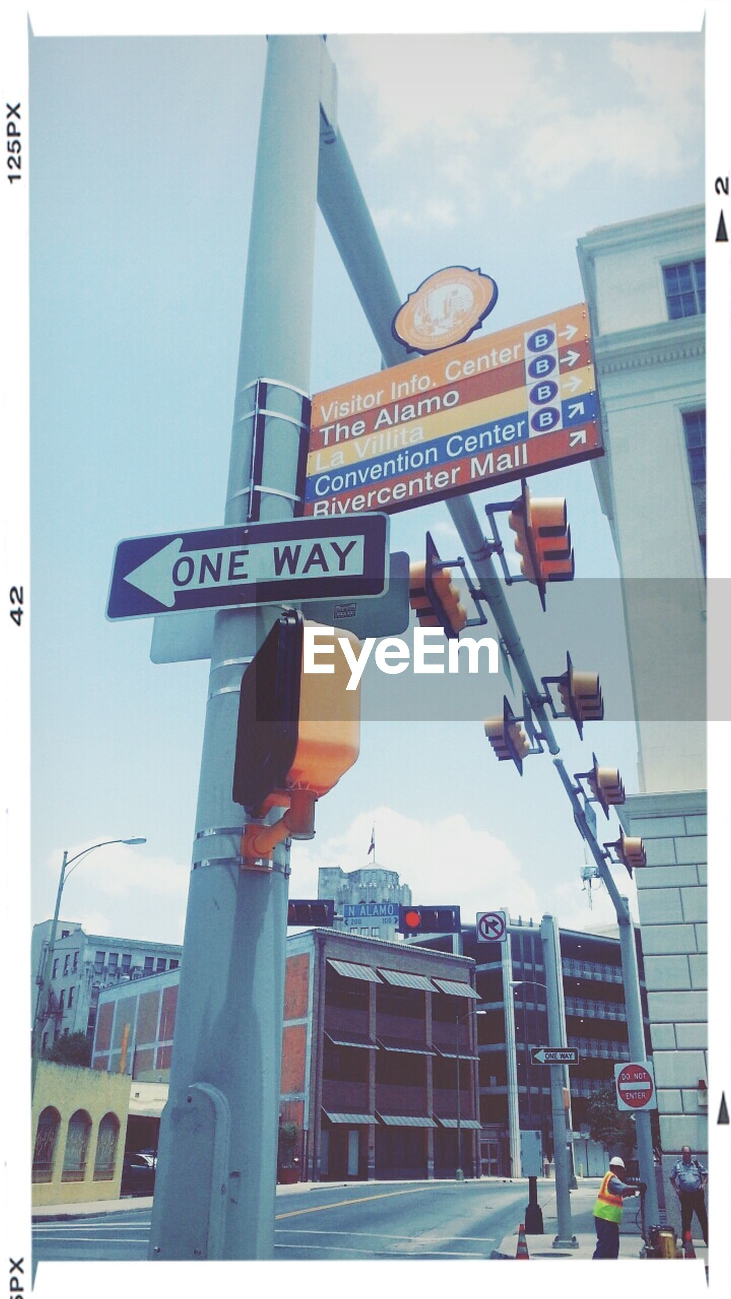 text, western script, communication, transfer print, low angle view, road sign, built structure, architecture, building exterior, guidance, information sign, sign, sky, information, city, street light, auto post production filter, directional sign, arrow symbol, non-western script