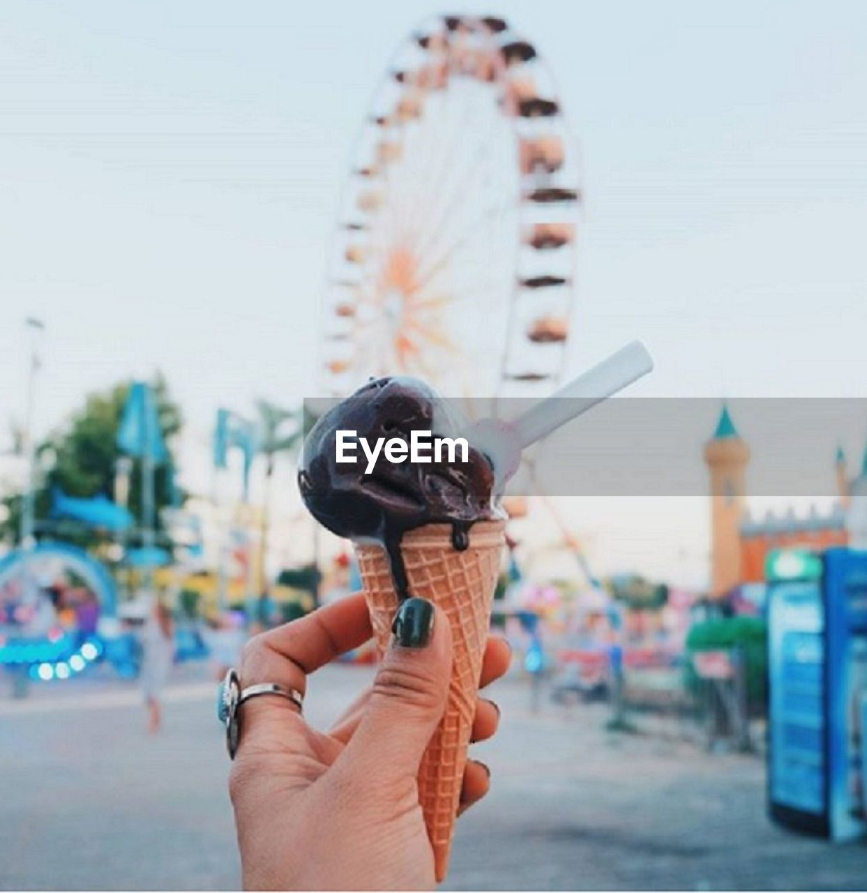 Cropped Hand Of Woman Holding Melting Ice Cream At Amusement Park