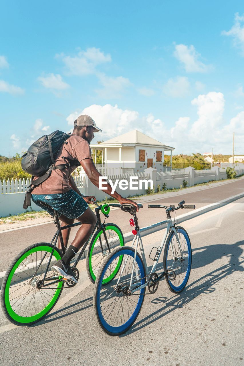 bicycle, transportation, real people, sky, city, sunlight, ride, riding, land vehicle, one person, cloud - sky, road, mode of transportation, day, nature, full length, architecture, casual clothing, lifestyles, outdoors