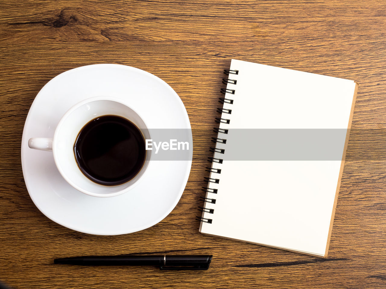 table, drink, coffee - drink, coffee, refreshment, pen, directly above, food and drink, spiral notebook, indoors, coffee cup, still life, cup, publication, mug, wood - material, black coffee, high angle view, book, no people, saucer, crockery, note pad, non-alcoholic beverage, blank