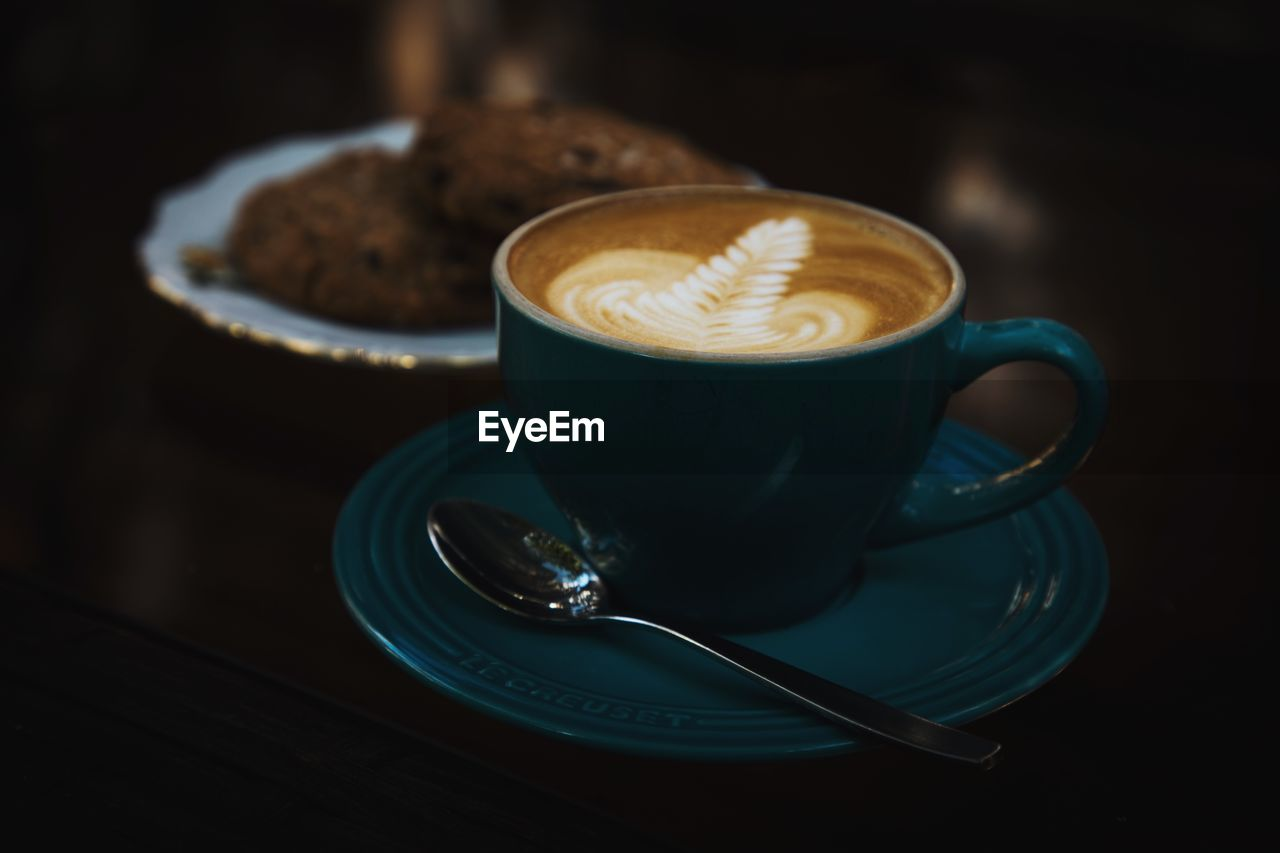 food and drink, coffee - drink, coffee, drink, coffee cup, refreshment, mug, cup, frothy drink, crockery, still life, eating utensil, hot drink, saucer, spoon, cappuccino, kitchen utensil, freshness, table, indoors, no people, latte, non-alcoholic beverage, temptation, teaspoon