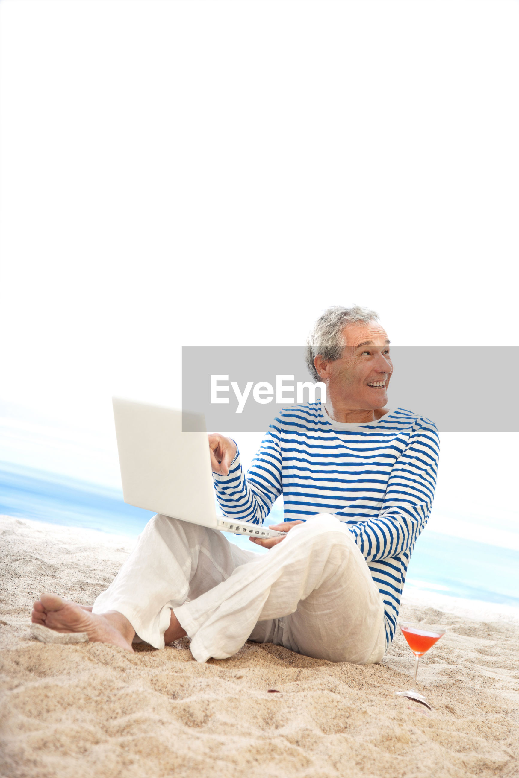 Man smiling while using laptop at beach against sky