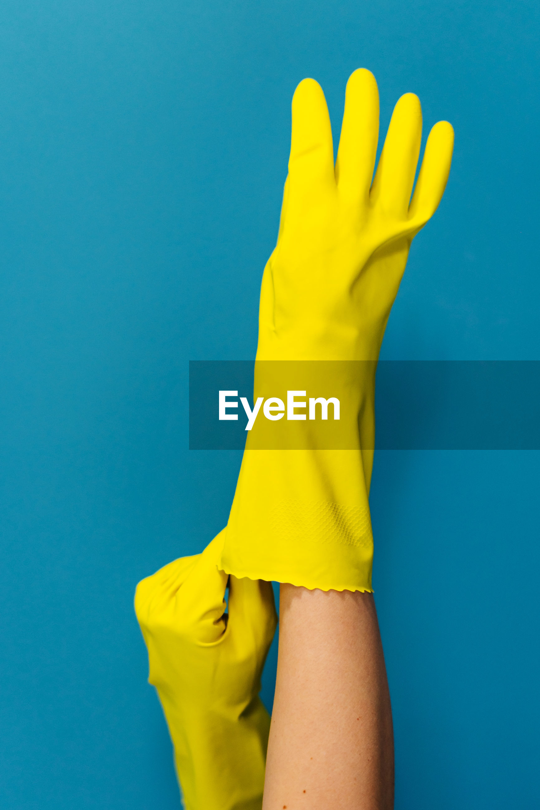 Cropped hand of woman wearing glove against blue background