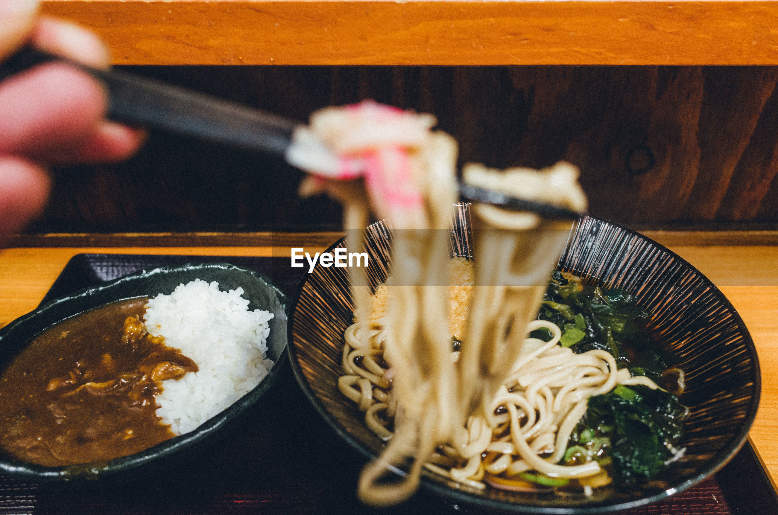 Cropped image of hand holding noodles in restaurant