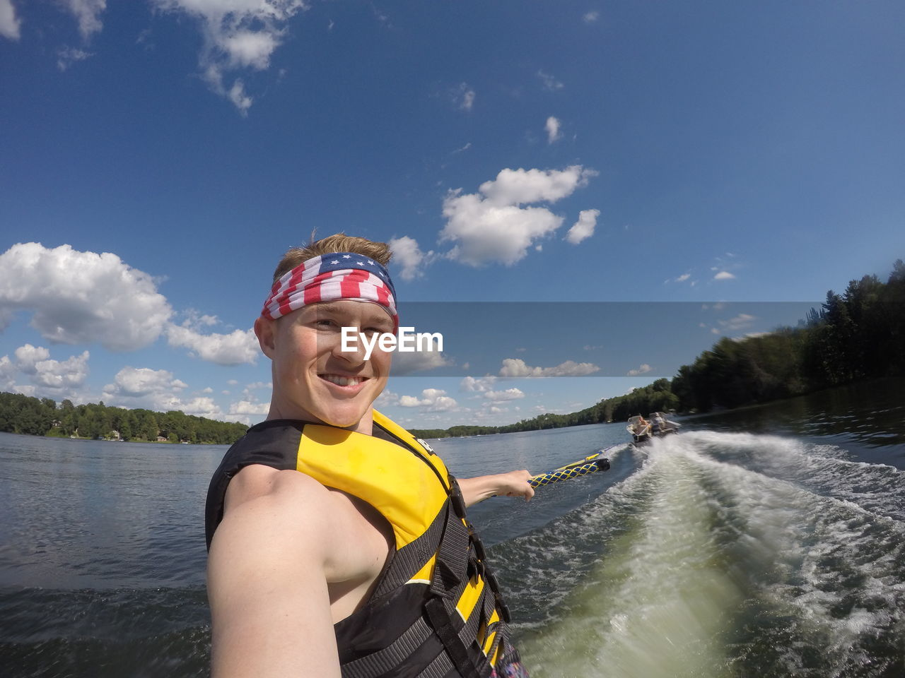 Portrait of smiling young man wakeboarding on lake against sky