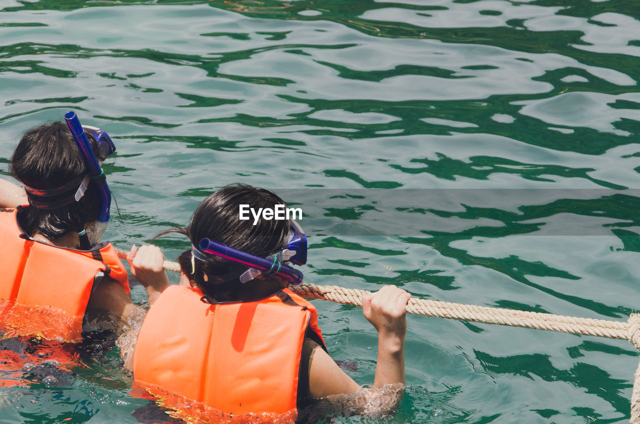 Rear view of people holding rope while snorkeling in sea