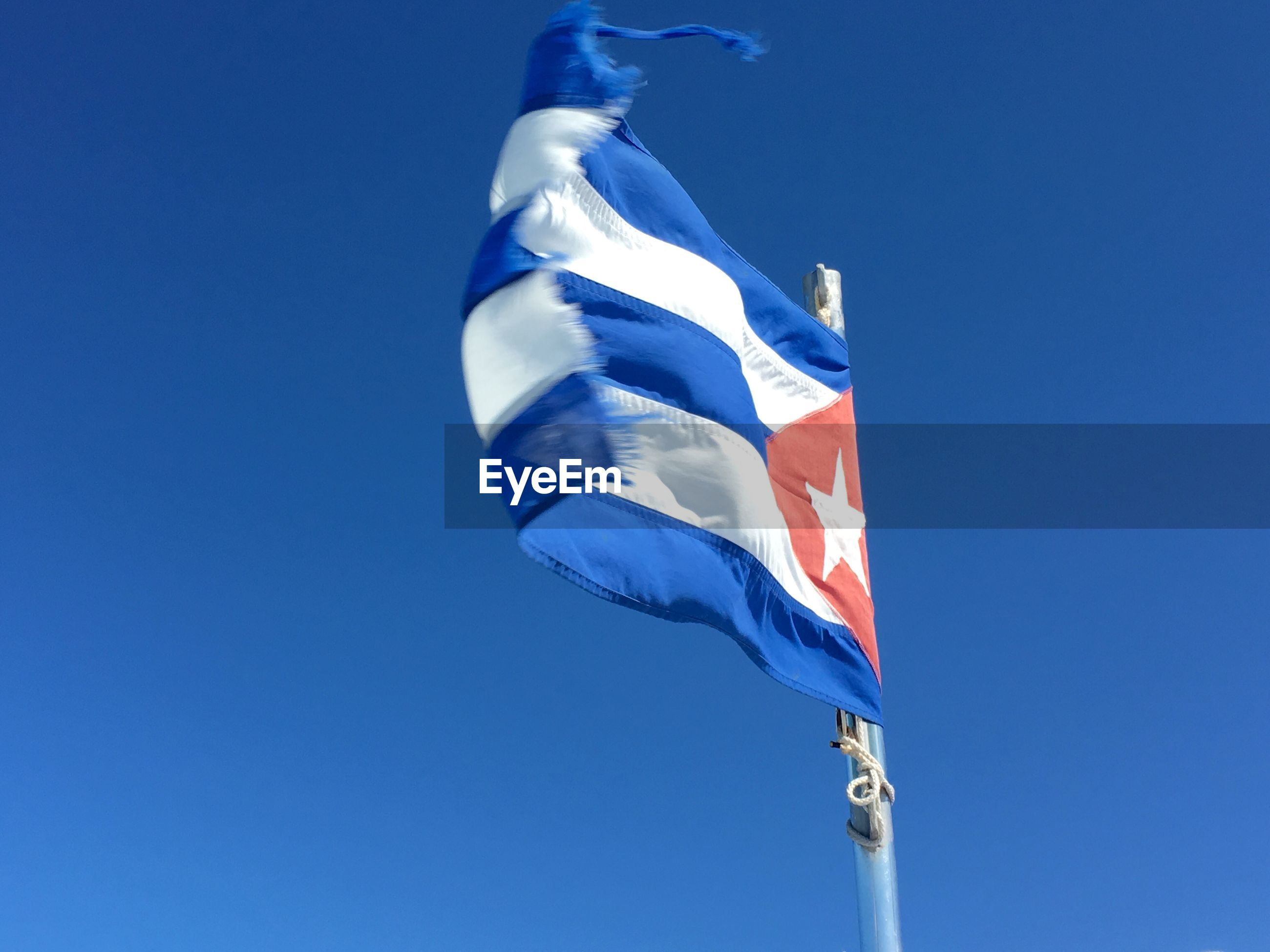 Low angle view of cuban flag waving against clear blue sky