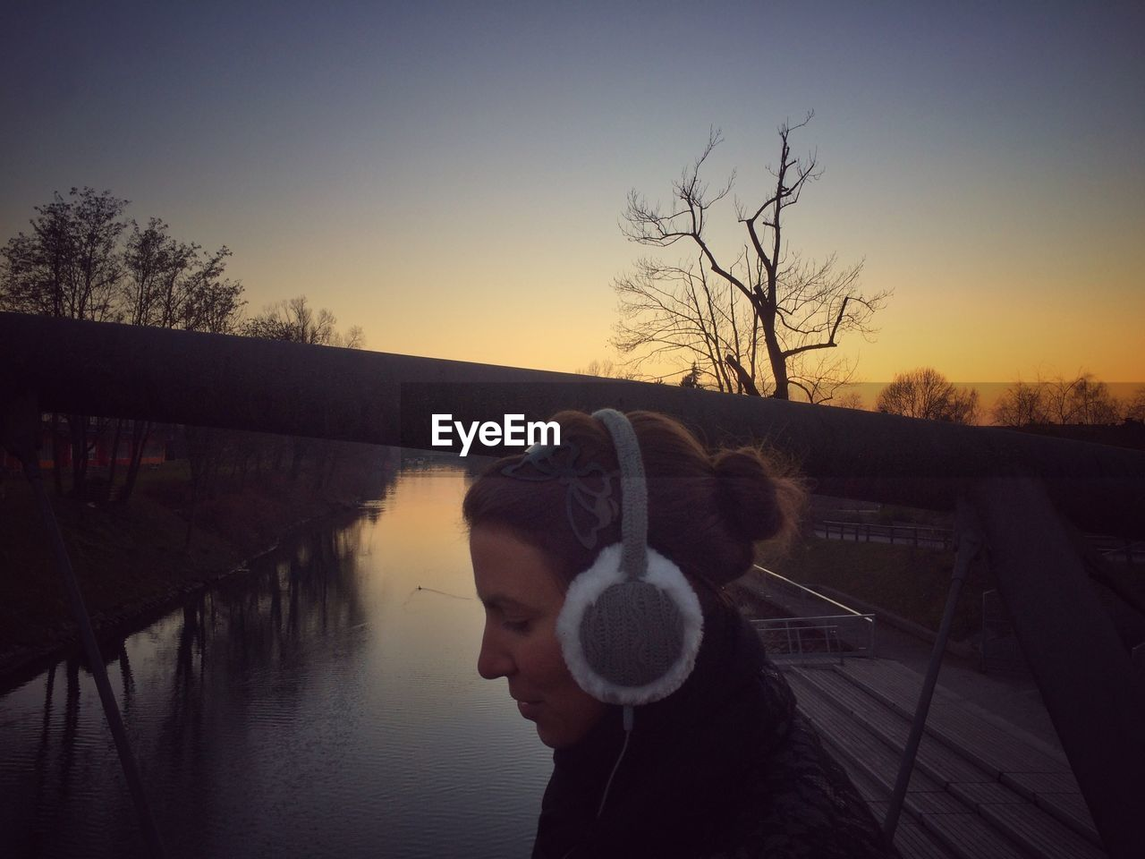 Woman listening music by stream during sunset