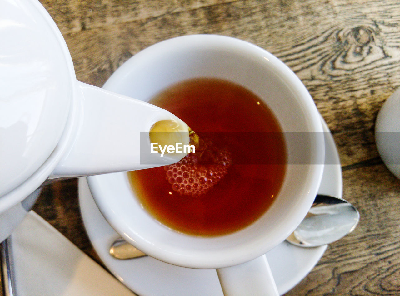 Close-up of teapot pouring tea in cup on table