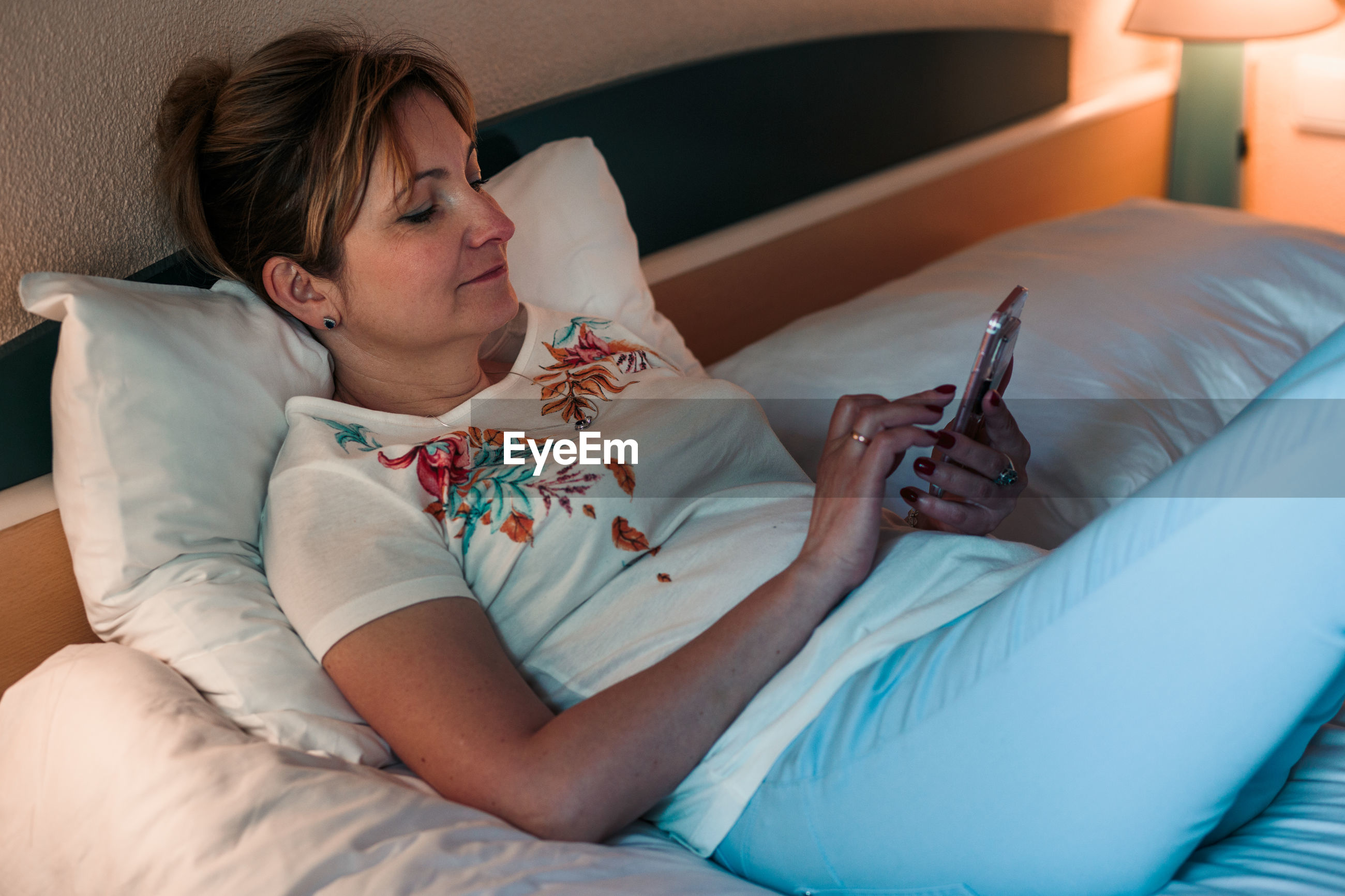 Woman using mobile phone on bed at home