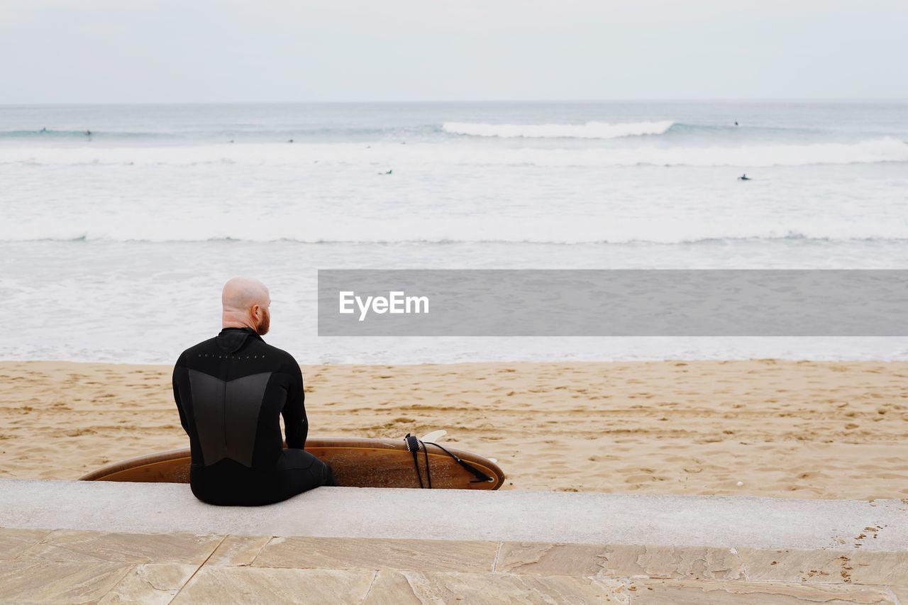 REAR VIEW OF MAN SITTING ON BEACH AGAINST SEA